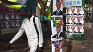 A man walks past posters of U.S. President Barack Obama and Senegal's President Macky Sall before Obama's visit in downtown Dakar June 26, 2013.