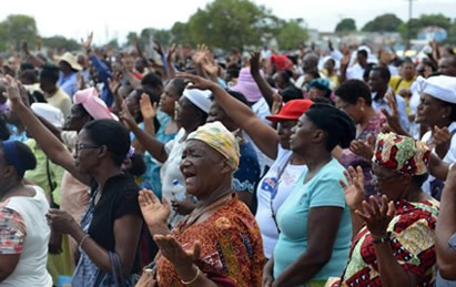 Jamaican churchgoers pray during an anti-gay rally in Kingston, Jamaica, Sunday, June 23, 2013. Several church pastors in Jamaica led a revival meeting Sunday to oppose efforts to overturn the Caribbean country's anti-sodomy law and turn back what they see as increasing acceptance of homosexuality. (AP Photo/David McFadden)