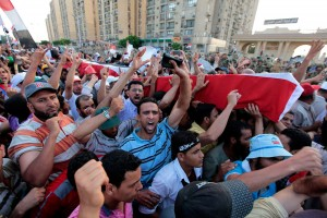 (Photo: Reuters/Louafi Larbi) Supporters of deposed Egyptian President Mohamed Mursi carry mock coffins during a symbolic funeral for the four men killed during clashes with police outside the Republican Guard headquarters a day earlier, in Cairo July 6, 2013. Egypt counted its dead on Saturday after Islamists enraged by the overthrow of Mursi took to the streets in an explosion of violence against what they denounced as a military coup.