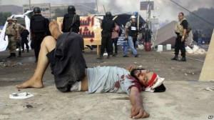 A wounded protester lies on the ground as Egyptian security forces clear the smaller of the two sit-ins by supporters of ousted Islamist President Mohammed Morsi, near the Cairo University campus in Giza, Cairo, Egypt, Aug. 14, 2013. Egyptian s