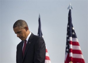 President Barack Obama lowers his head during a moment of silence at the Pentagon, Wednesday, Sept. 11, 2013, during a ceremony to mark the 12th anniversary of the 9/11 attacks. (AP Photo/Pablo Martinez Monsivais)