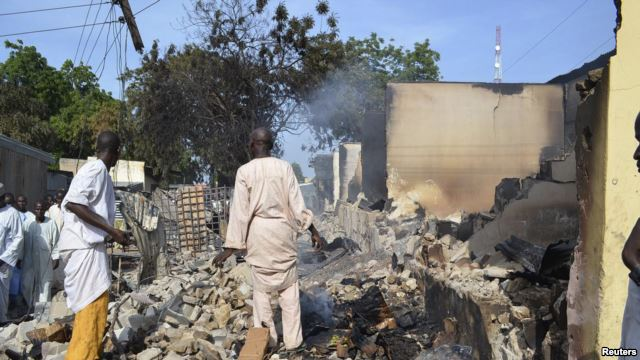 Residents watch as two men walk amidst rubble after Boko Haram militants raided the town of Benisheik, west of Borno State capital Maiduguri, Sept. 19, 2013.