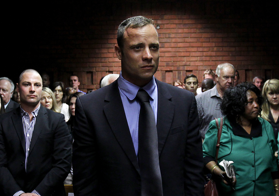 (Photo: Reuters/Siphiwe Sibeko) Oscar Pistorius awaits the start of court proceedings while his brother Carl (L) looks on, in the Pretoria Magistrates court February 19, 2013. Pistorius, a double amputee who became one of the biggest names in world athletics, was applying for bail after being charged in court with shooting dead his girlfriend, 30-year-old model Reeva Steenkamp, in his Pretoria house.