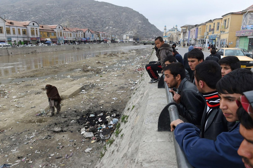 Afghan residents look at the site where an Afghan woman was beaten to death and her body set alight by a mob, in Kabul on March 20, 2015.