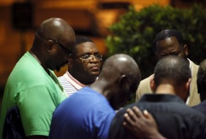 A small prayer circle forms nearby where police are responding to a shooting at the Emanuel AME Church in Charleston, South Carolina, June 17, 2015. A gunman opened fire on Wednesday evening at the historic African-American church in downtown Charleston and was still at large, a U.S. police official said, but there were no immediate confirmed reports of casualties. Read more at http://www.christianpost.com/news/white-gunman-kills-pastor-8-others-during-bible-study-at-historic-black-church-in-south-carolina-police-label-act-as-hate-crime-140560/#OETmcVOtLkWZzqcr.99