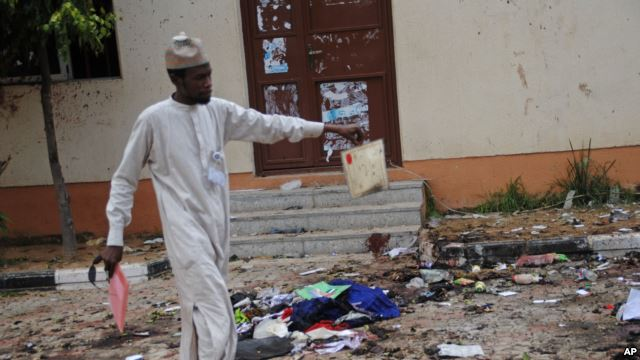 FILE - A man picks up an item belonging to a student at the site of a bomb blast in the university town of Zaria, Nigeria, July 7, 2015.